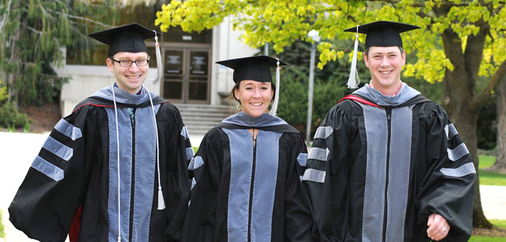 Career, Job Search & Graduate Student Resources, photo of three graduate students in regalia